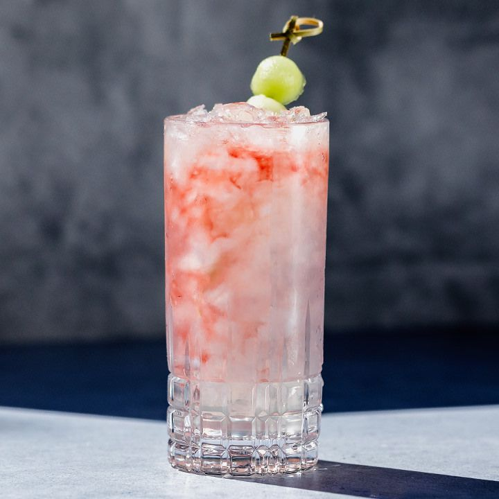 A Collins glass containing a translucent white cocktail with swirls of red raspberry liqueur, garnished with a skewered honeydew melon ball
