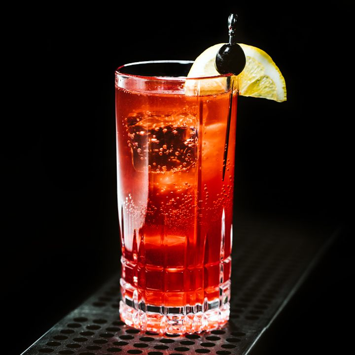Sloe Gin Fizz cocktail with cherry and lemon garnish, served on a metal bar grate