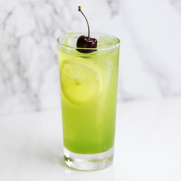 bright-green tokyo tea cocktail with lemon wheel and cherry garnishes