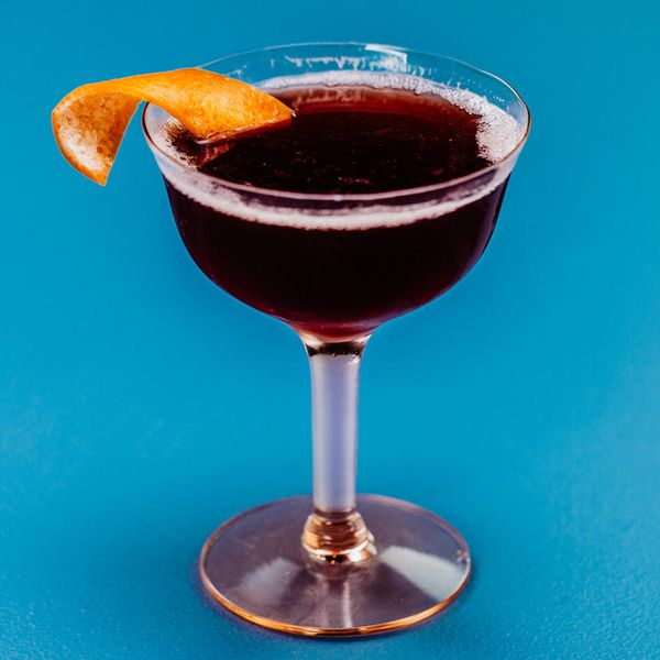 deep burgundy-colored Improved Dunlop cocktail in a coupe, with a grapefruit peel garnish