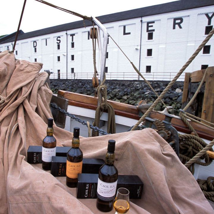 Caol Ila Distillery with a bunch of their bottles laid out artfully on a tarp in a boat