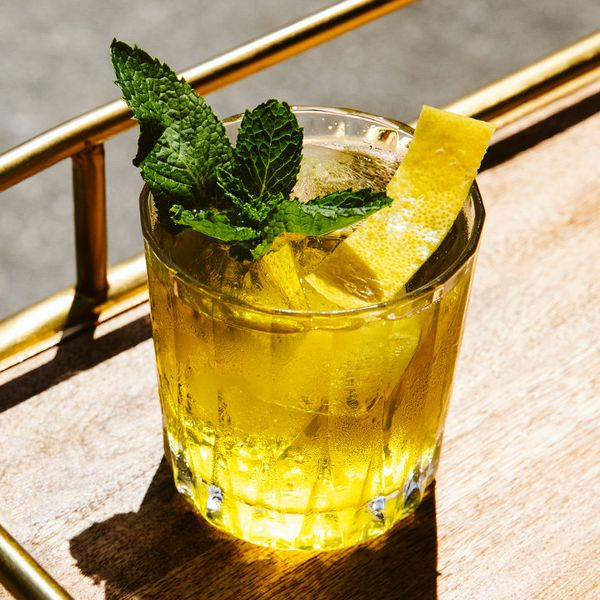An elegant, faceted rocks glass holds a vividly golden elixir with large cubes of ice. A single trimmed lemon peel and a small mint sprig garnish the drink, which rests on a wooden bar tray.