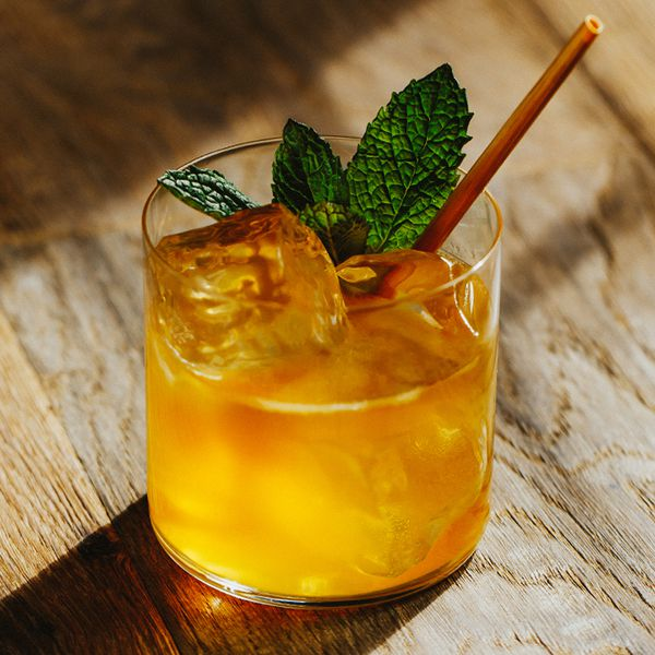 Whiskey Smash cocktail on ice with mint leaves and a straw