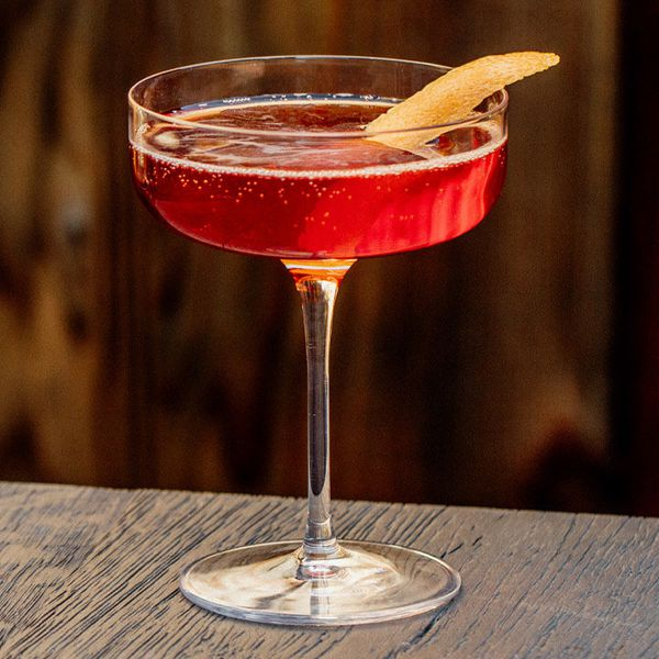 A flat coupe glass rests on the edge of a dark wooden table. The drink within is red and bubbly, and garnished with an orange peel.