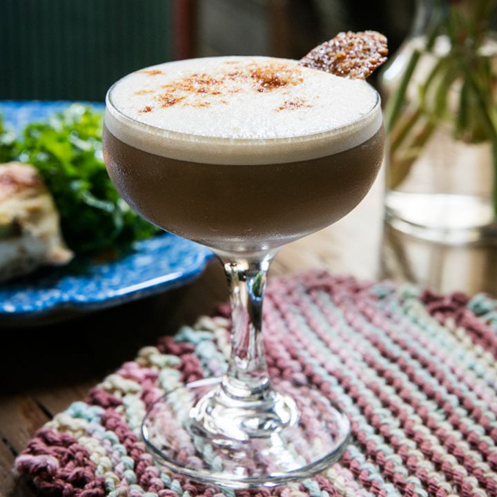 In a busy photo, a coupe glass sits on a colorfully knitted mat. The glass holds a dark brown cocktail with a foamy white head dotted with bitters and garnished with a thin cookies. A plate of food and a bottle of water are in the background.