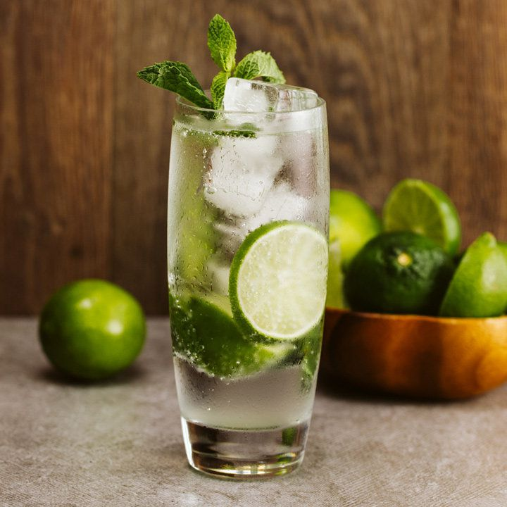 A mojito in a thin Collins glass is centered in the photo. The glass is filled with ice cubes, rings of limes, and bubbly water, and is topped with mint. In the background, out of focus, lies a single lime, as well as a bowl of limes and lime halves.