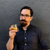 A man with dark hair and beard with a long mustache and glasses leans against a gray wall. He is holding a cocktail and wearing a blue shirt with white dots.