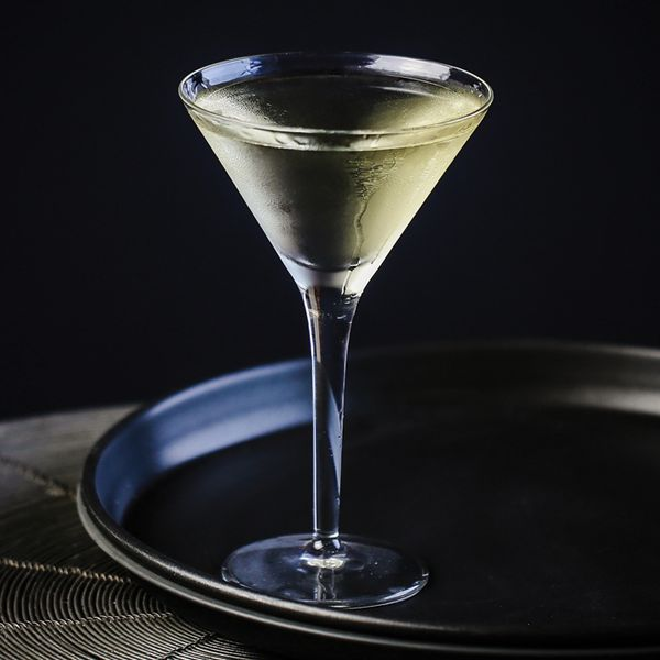 A chilled, yellow-hued Martini served in a clear Martini glass on a round black tray