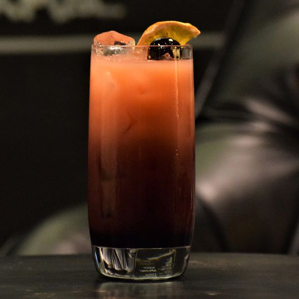 A Collins glass rests on a black surface in front of a black leather chair. The drink within is dark red at the base and lightens to orange as it gets to the top.