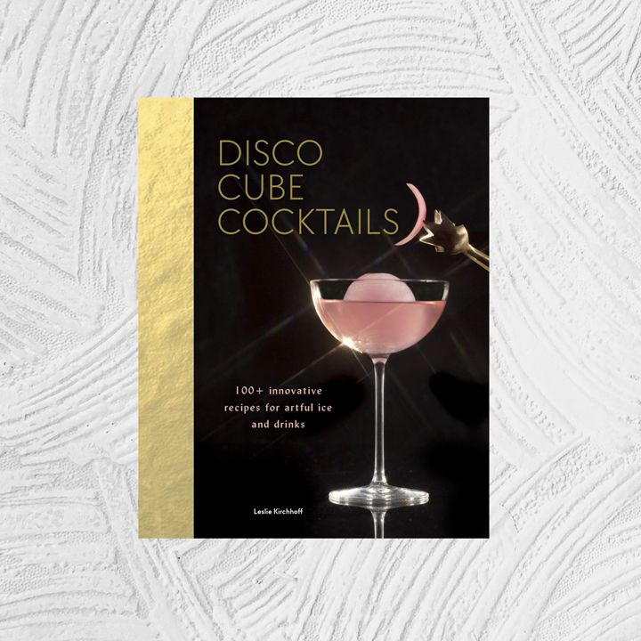Disco Cube Cocktails: 100+ Innovative Recipes for Artful Ice and Drinks cover with gold leaf-esque binding and a black background; pictured is a pink cocktail in a slim coupe with an ice sphere and seventies-inspired light reflections