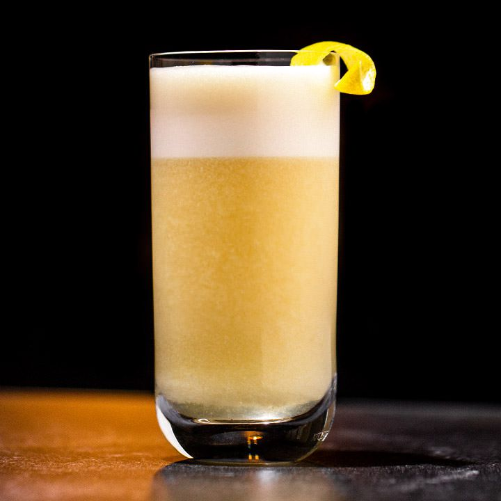 A clear, straight walled highball glass is filled with a foamy, bubbly copper-colored drink topped with a thick layer of foam. It's garnished with a small lemon peel. The background of the photo is black, and the drink is dramatically lit, resting on a bar top.
