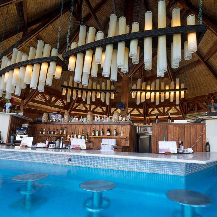 The St. Regis Bora Bora swim-up bar. Pillar-like light fixtures hang in tight groups from the ceiling