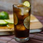 Cuba Libre cocktail next to a wooden cutting board and limes
