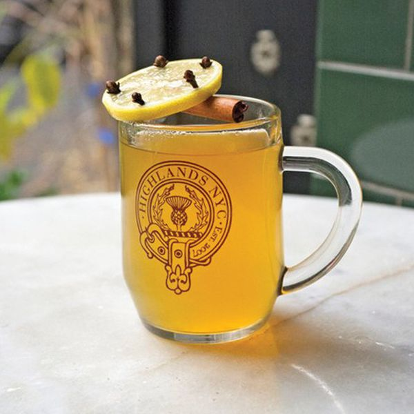 """A handled, clear glass mug is branded with an emblem that reads """"Highlands NYC Est. 2007."""" The mug sits on a marble table and is filled with a pale golden drink. It's garnished with a cinnamon stick and a clove-studded lemon wheel."""