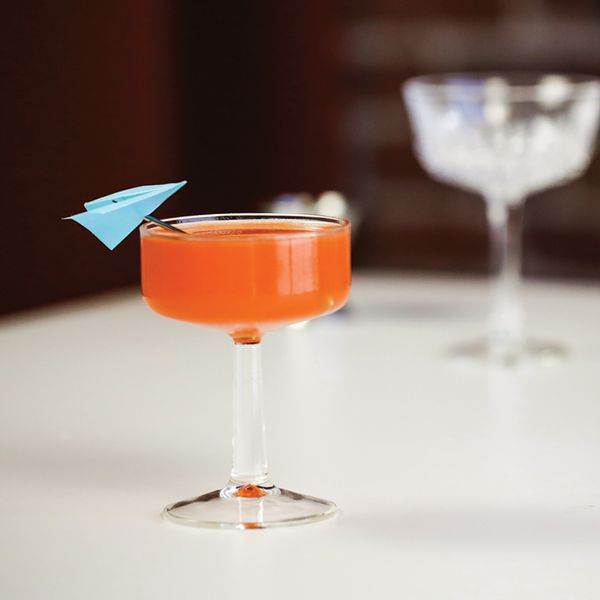 paper plane cocktail in a coupe, garnished with a miniature blue paper plane