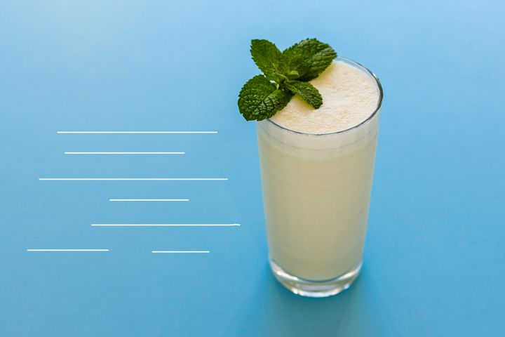 A frothy, cream-colored Absinthe Suisse cocktail in a Collins glass garnished with fresh mint