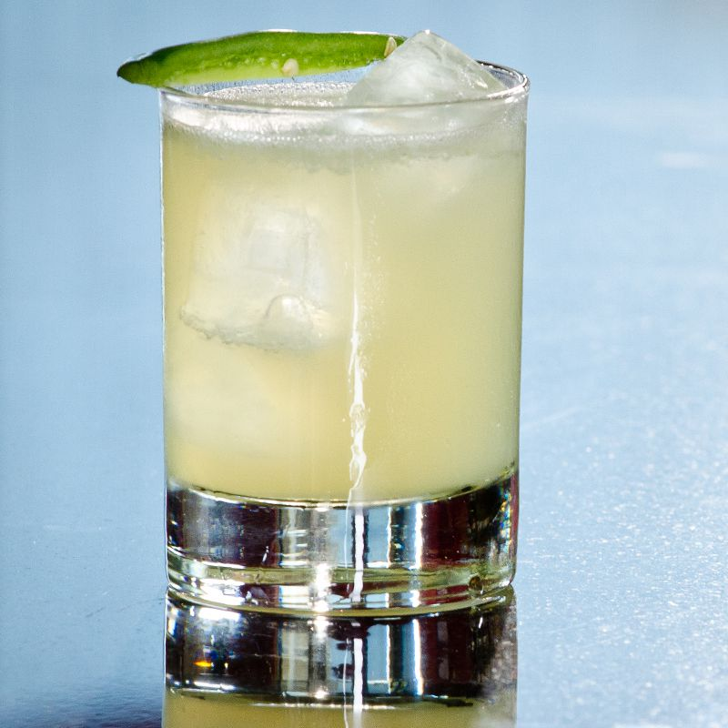 A double rocks glass rests on a reflective surface. The glass holds a yellow-green cocktail with ice cubes, and is garnished with a sliver of jalapeño.