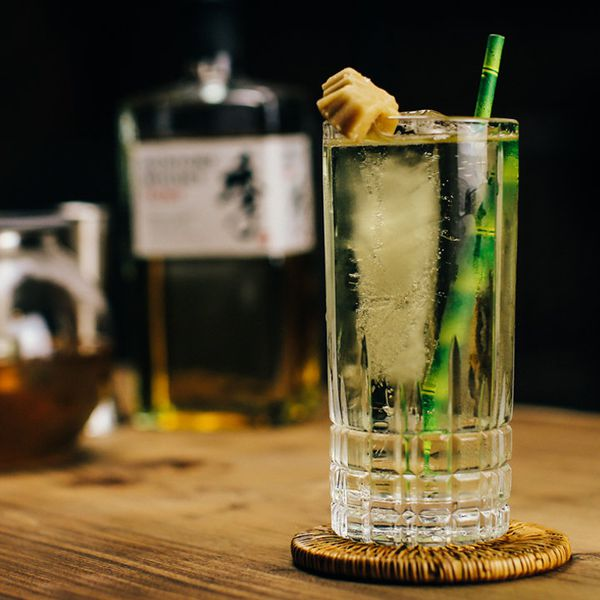 In the foreground, a Collins glass with a faceted bottom rests on a wicker coaster. It's filled with a green highball, a spear of ice, a fake bamboo straw and a maple leaf candy garnish. In the background out of focus is a bottle of Japanese whisky.