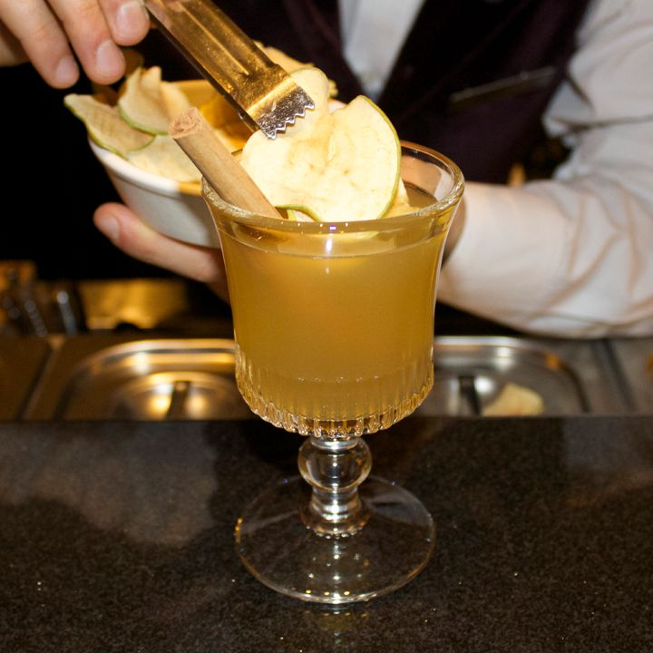 hand places dried apple garnish on the Hot Apple Pie cocktail, served in an Irish Coffee glass with a cinnamon stick