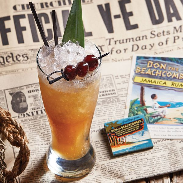 A footed pilsner glass holds a dark rum drink and crushed ice, garnished with a pineapple frond and three cherries skewered on a sword-shaped pick. The drink rests on a newspaper announcing the Allies' victory over the Axis in World War II, as well as some Tiki ads.