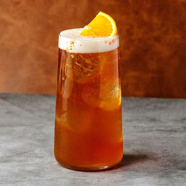 A Collins glass filled with a reddish-brown beer cocktail, garnished with an orange half wheel on a head of foam