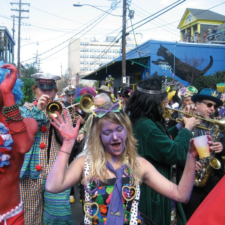 mardi Gras revelers with a woman in the cetner in purple face point and a trumper player behind her
