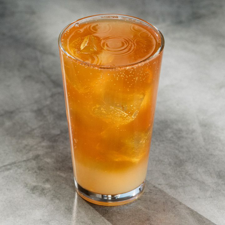 A pint glass filled with a light amber-hued cocktail and set on a gray stone tabletop
