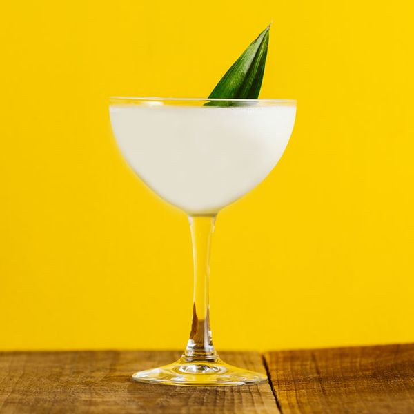 A creamy white cocktail in a coupe glass garnished with a pineapple leaf, set on a wood surface against a bright yellow background