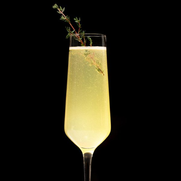A narrow Champagne flute holds a bubbly yellow drink garnished with a sprig of thyme. It glows brightly against a black background