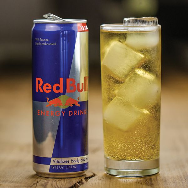 Vodka Red Bull in a glass with ice next to a can of Red Bull