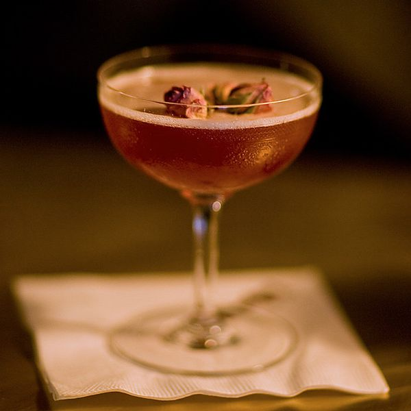 Mata Hari Cocktail in a coupe, garnished with two dried rosebuds and served on a white bar napkin