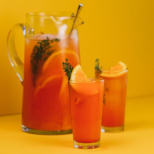 red-orange summerthyme screwdriver in a pitcher alongside two full Collins glasses, each garnished with a thyme sprig and orange wheel