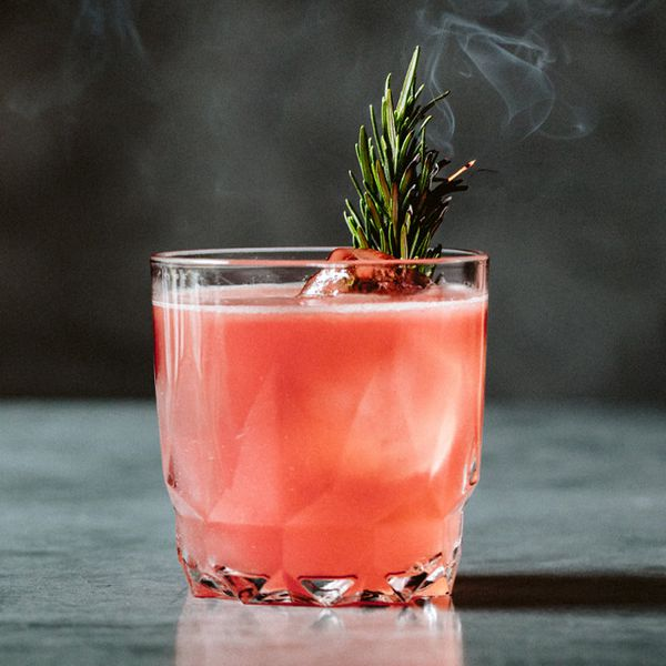 A faceted rocks glass rests on a gray marble surface. The glass is filled with a light red drink, some ice cubes and a gently smoking sprig of rosemary.