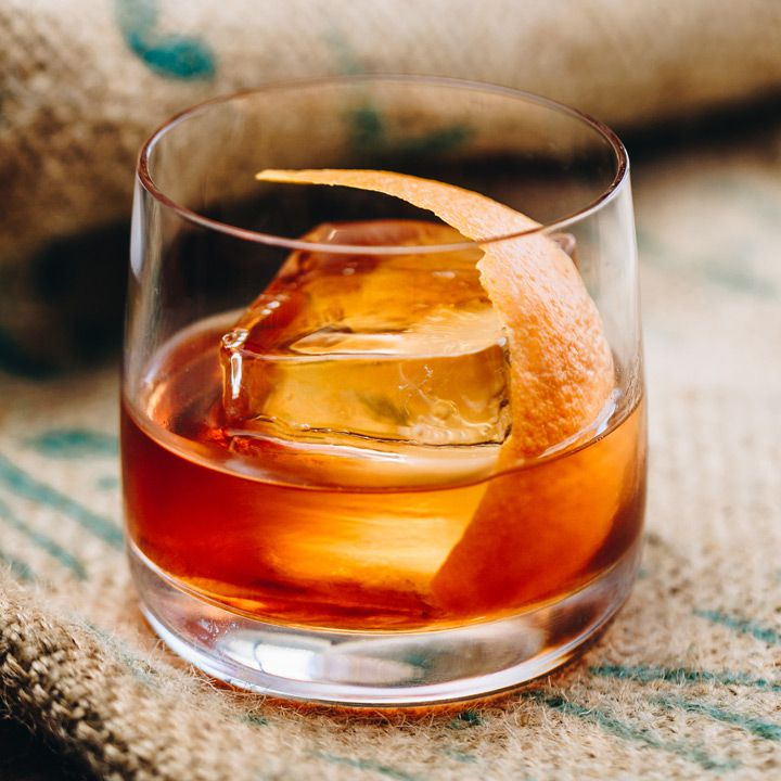 A dark, caramel colored Old Fashioned in a thin-walled rocks glass, with a single large ice cube and a curved swath of orange peel sits on burlap