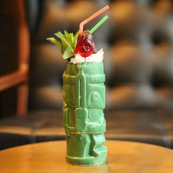 A green Tiki mug shaped like Star Wars's Boba Fett is garnished with a Darth Vader gummy, a sprig of mint, and two twisty straws
