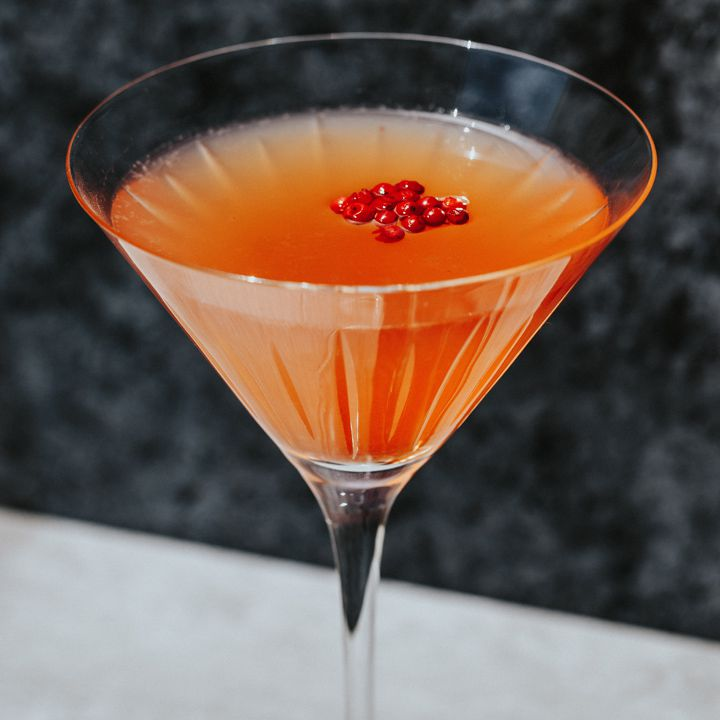 A vidid red-orange cocktail served in a Martini glass, the Ile Rouge is named for the small island of peppercorns floating on its surface.