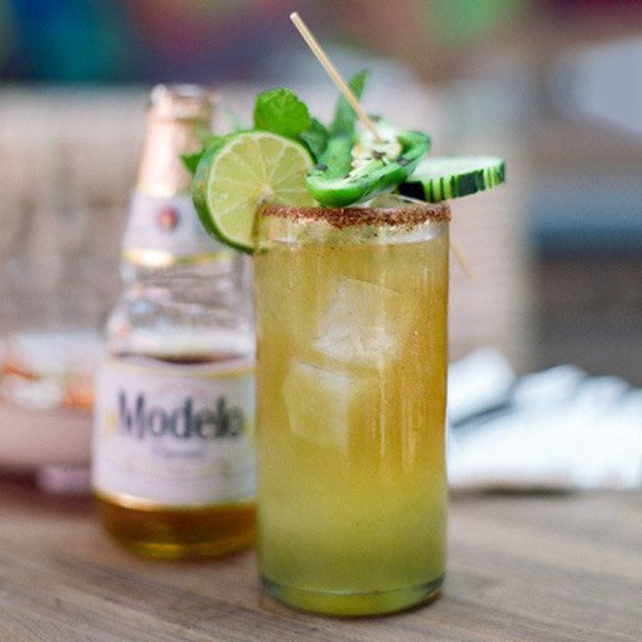 The focus is on a highball glass filled with ice and a drink that shifts from orange to green as it goes top to bottom. The glass is rimmed with spicy salt, and garnished with jalapeño, mint, cucumber, and lime. In the background, out of focus, is a Modelo bottle.
