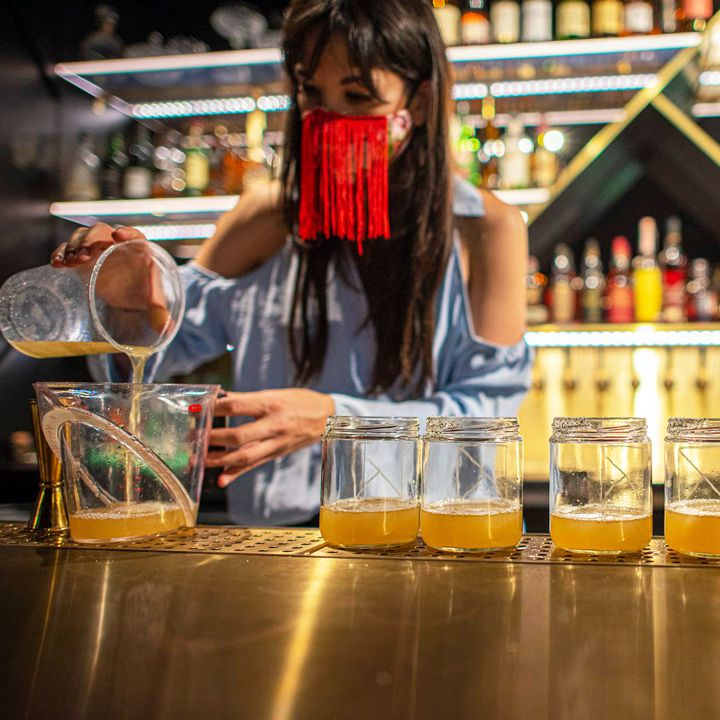 A bartender prepares to-go cocktails wearing Ashley Roshitsh's handmade mask.