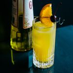 harvey wallbanger cocktail with orange-and-cherry garnish, plus a bottle of Galliano