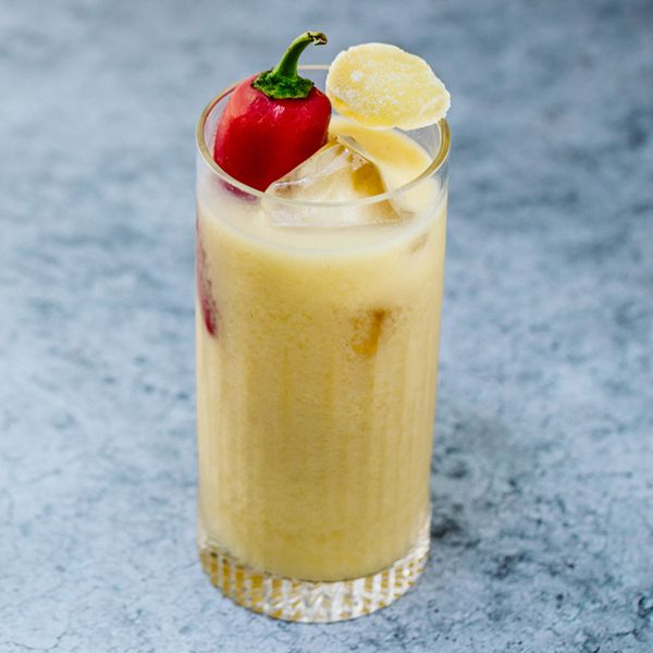 A Collins glass rests on a marbled stone surface. The glass is filled with ice cubes, a frothy yellow drink and a large red pepper. A candied piece of ginger rests atop.