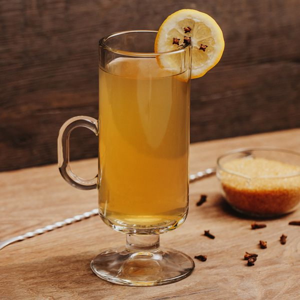 Hot Toddy cocktail in a glass mug with lemon wheel and cloves