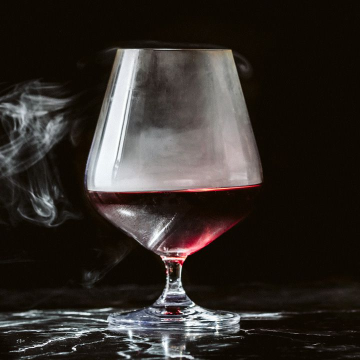 A large snifter rests on a black marble surface against a sold black backdrop. The snifter contains a dark red drink and whiffs of smoke which emanate from the glass.