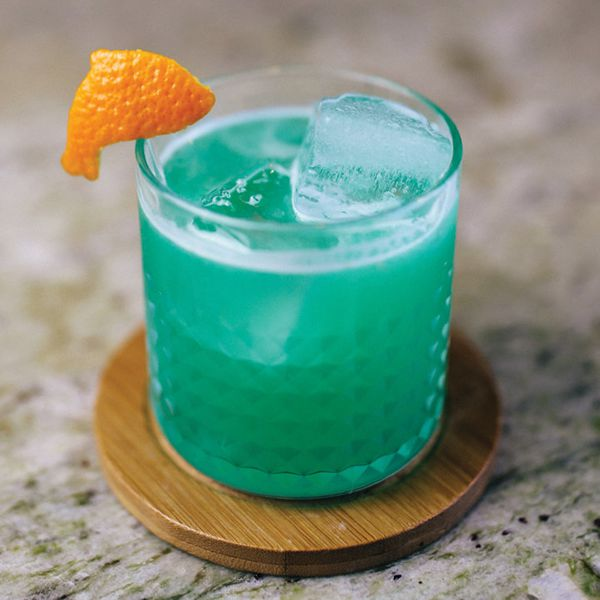 blue-colored Spirit of '72 cocktail in a textured rocks glass, garnished with a dolphin-shaped orange peel and served on a round wooden coaster