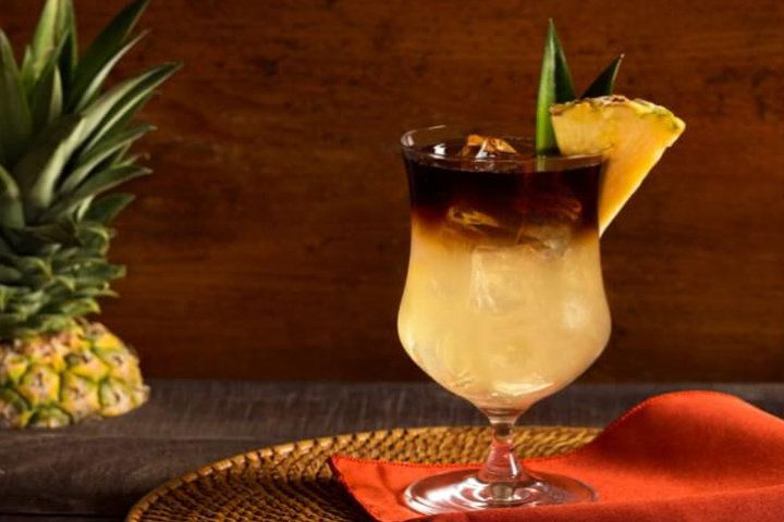 A Mai Tai in a clear stemmed glass with a black rum float and pineapple garnish