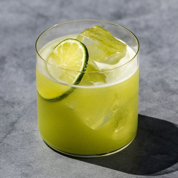 A thin-walled rocks glass sits on a gray concrete surface. The glass holds a vivid green cocktail over ice, garnished with a lime wheel.