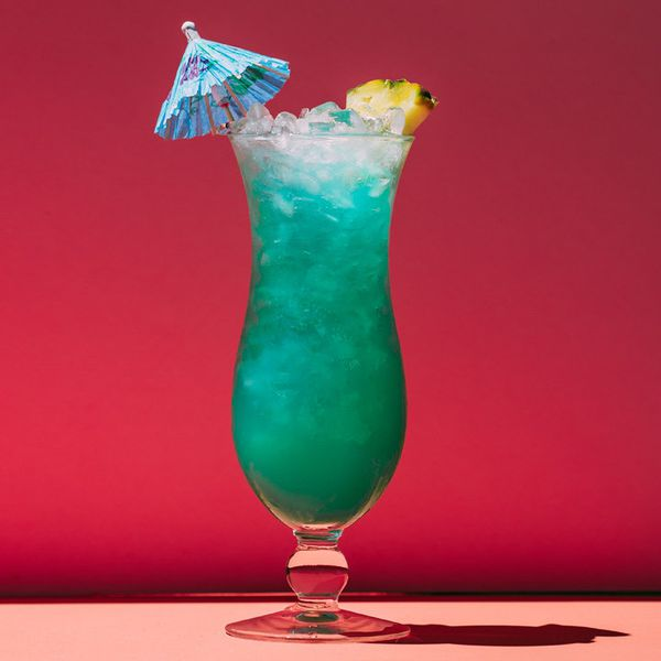blue hawaii cocktail with paper umbrella against a red background