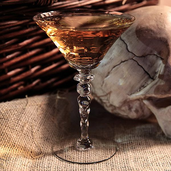 A Martini glass with a knobbed stem sits on burlap cloth. Behind it are a wicker basket and a human skull. The glass holds a light brown-orange drink.