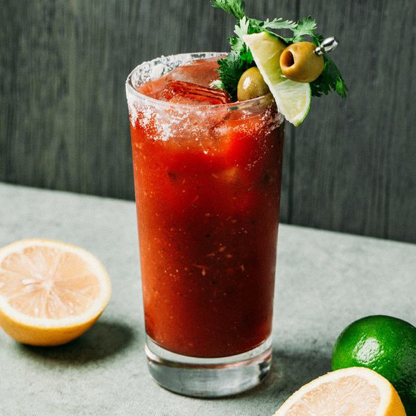 A Bloody Mary in a Collins glass rimmed with salt and garnished with cilantro, green olives, and a lime wedge