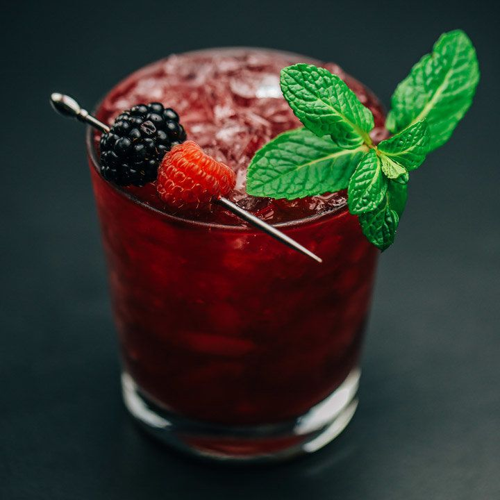 A deep purple cocktail over crushed ice in a rocks glass garnished with skewered berries and a mint sprig