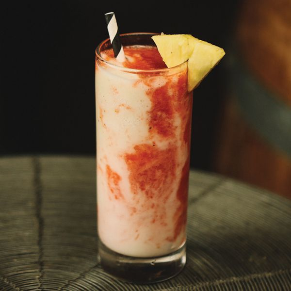 red-and-white frozen Lava Flow cocktail in a highball glass, with black-and-white straw and pineapple wedge